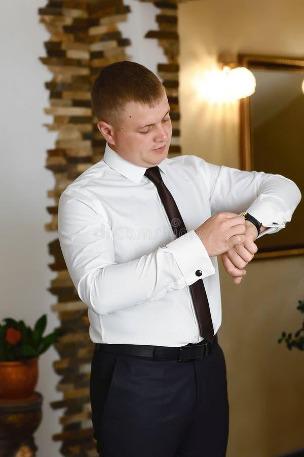 Un hombre que arregla sus ojales en un fondo de una camisa blanca, reloj que lleva del novio el día de boda camisa con mangas y r imágenes de archivo libres de regalías