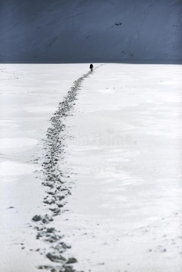 Un hombre que camina un camino en la nieve en las montañas Paisaje de la montaña del invierno imagen de archivo