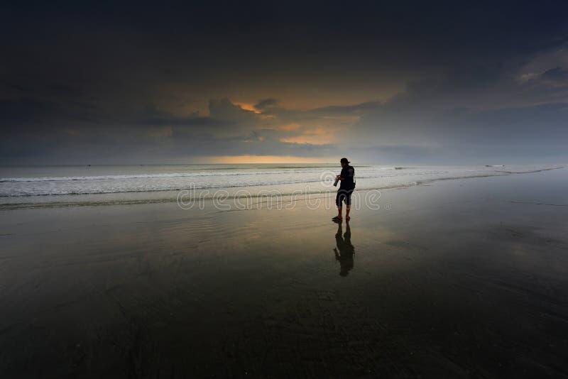 Un hombre que camina en una playa fotos de archivo libres de regalías