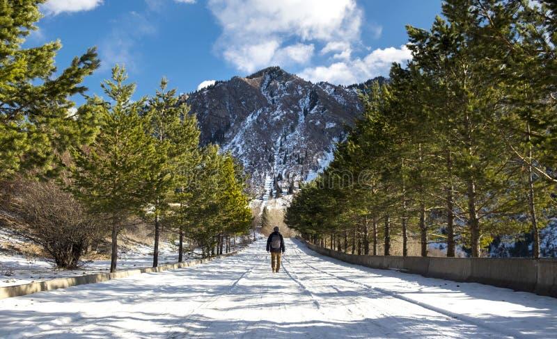 Un hombre que camina hacia una montaña en invierno imagen de archivo libre de regalías