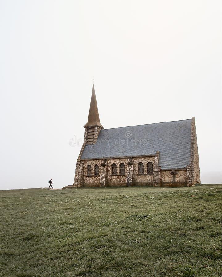 Un hombre que camina a la iglesia medieval de piedra vieja del normando del pueblo en Europa con la hierba verde en primero plano imágenes de archivo libres de regalías