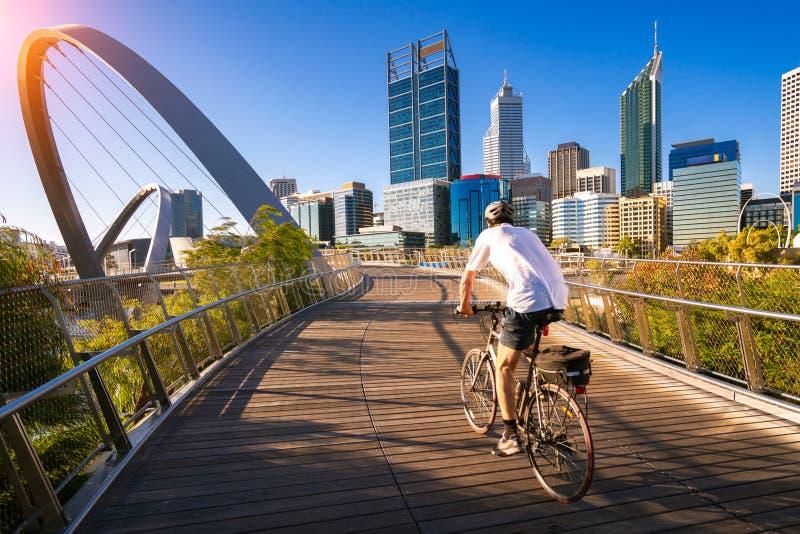 Un hombre que completa un ciclo en un puente de Elizabeth en la ciudad de Perth fotos de archivo