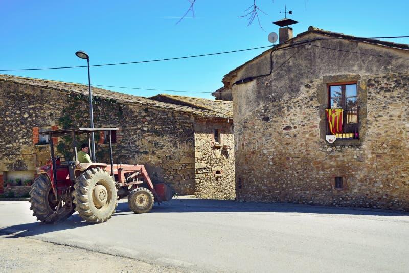 Un hombre que conduce un tractor en el pueblo Sant-Esteve-de-Guialbes españa imagen de archivo