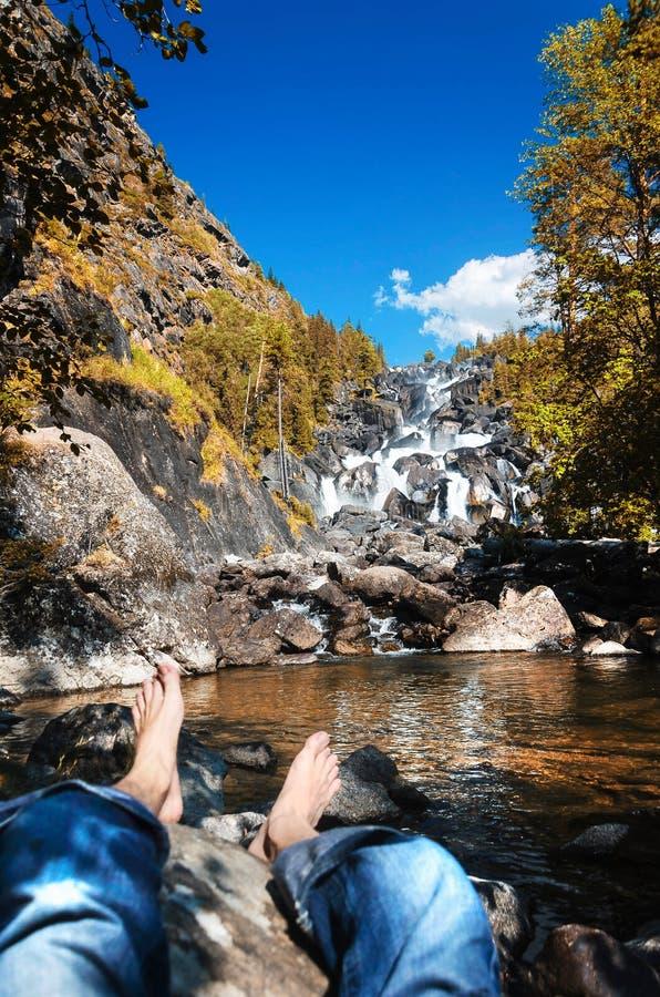 Un hombre que descansa en la cascada en las montañas de Altai, república de Altai, Siberia, Rusia de Uchar imagenes de archivo