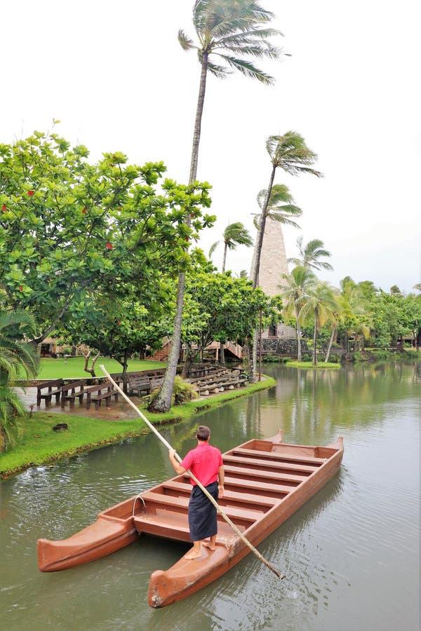 Un hombre que dirige un barco de la canoa en una peque?a corriente en el centro cultural polinesio imagenes de archivo