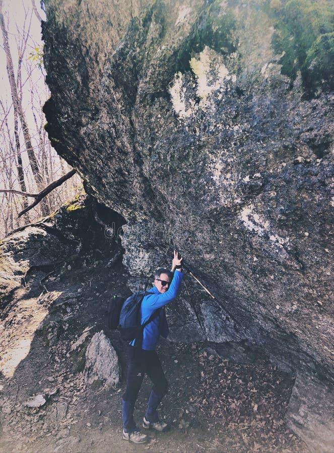 Un hombre que empuja una roca grande imagenes de archivo