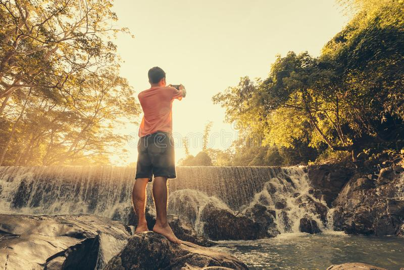 Un hombre que gozaba de la cascada tropical asombrosa aumentó las manos viaja las vacaciones de la forma de vida y del concepto d fotografía de archivo