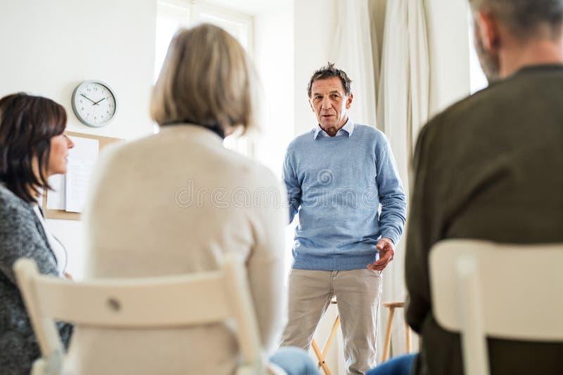 Un hombre que habla con otras personas durante terapia del grupo fotografía de archivo