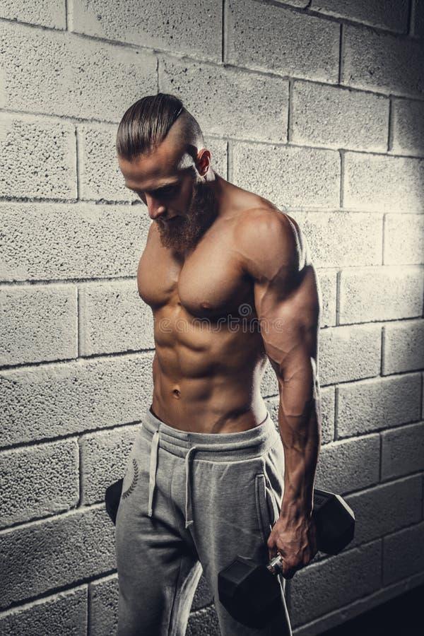 Un hombre que hace ejercicios del bíceps con pesas de gimnasia imágenes de archivo libres de regalías