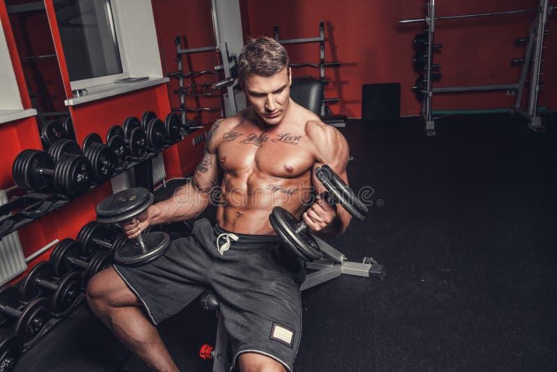 Un hombre que hace entrenamiento del bíceps imagen de archivo libre de regalías
