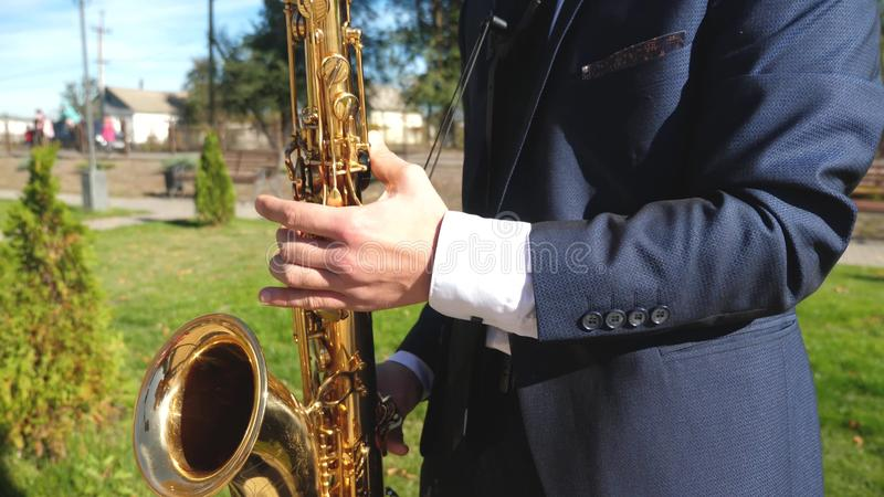un hombre que juega música de jazz del saxofón Saxofonista en juego de la chaqueta de cena en el saxofón de oro Actuación en dire fotografía de archivo