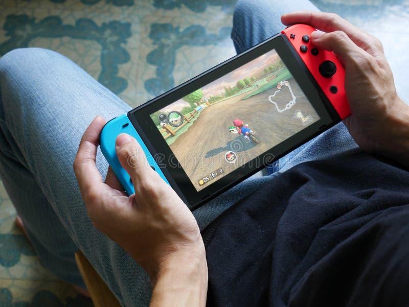 Un hombre que juega a Mario Kart 8 de lujo en el interruptor de Nintendo imágenes de archivo libres de regalías