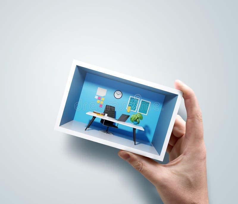 Un hombre que lleva a cabo un espacio de oficina miniatura en su mano fotografía de archivo