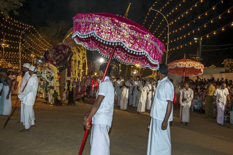 Un hombre que lleva un paraguas ceremonial espera como el elefante más sagrado en los desfiles del festival de Kataragama a travé imagenes de archivo