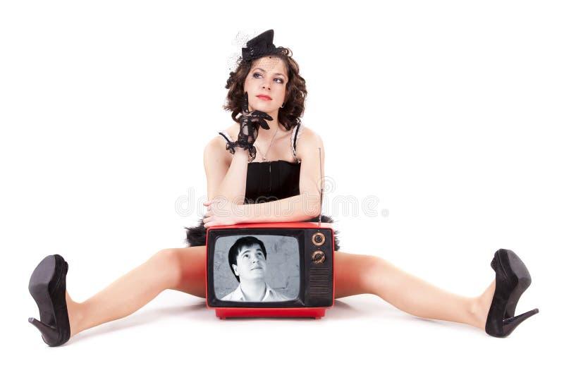 Un hombre que mira en la muchacha a través del tubo viejo de la TV imágenes de archivo libres de regalías