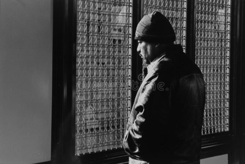 Un hombre que mira fijamente afuera la estación de tren en Jackson Heights fotografía de archivo