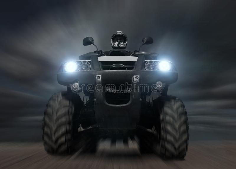 Un hombre que monta ATV en arena en casco protector fotografía de archivo