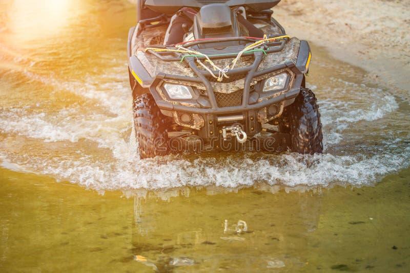 Un hombre que monta el vehículo todo terreno ATV va a lo largo del lago o del río foto de archivo libre de regalías