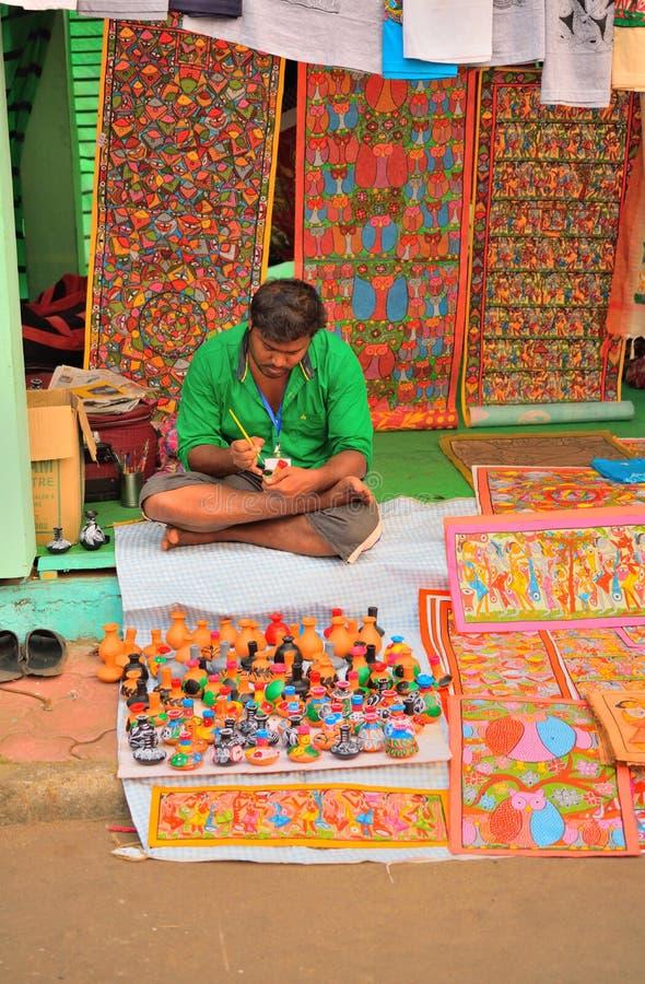 Un hombre que pinta un pote en un local justo fotos de archivo libres de regalías