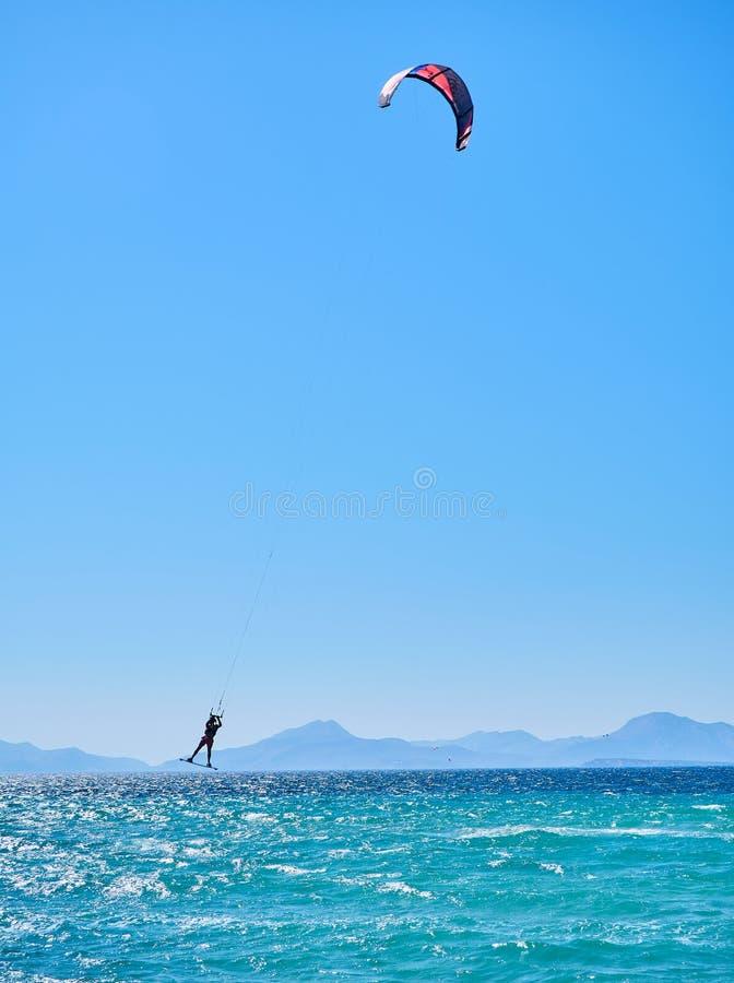 Un hombre que practica Kitesurf en una playa de Kos Grecia imagen de archivo