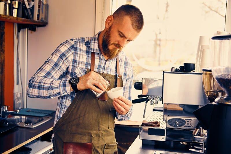 Un hombre que prepara capuchino en una cafetería imagen de archivo libre de regalías