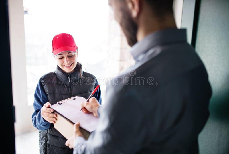 Un hombre que recibe el paquete de mujer de la entrega en la puerta imagen de archivo libre de regalías