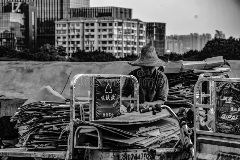 Un hombre que recoge la basura en el mercado de la industria pesquera de Huangsha imagenes de archivo