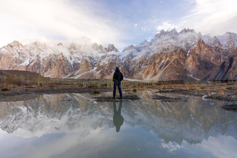 Un hombre que se coloca en el valle y la reflexión de la catedral de Passu en el agua en Paquistán septentrional foto de archivo libre de regalías