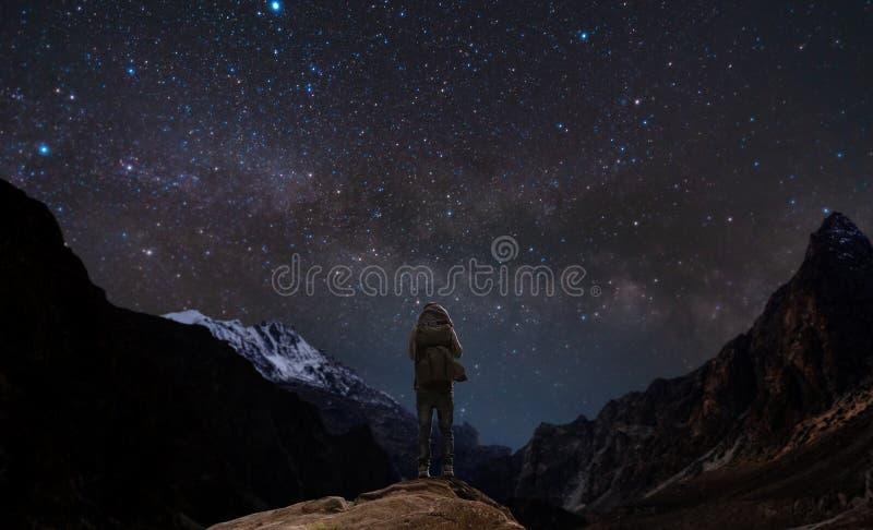 Un hombre que se coloca en pico y el cielo nocturno de montaña por completo de la estrella imágenes de archivo libres de regalías
