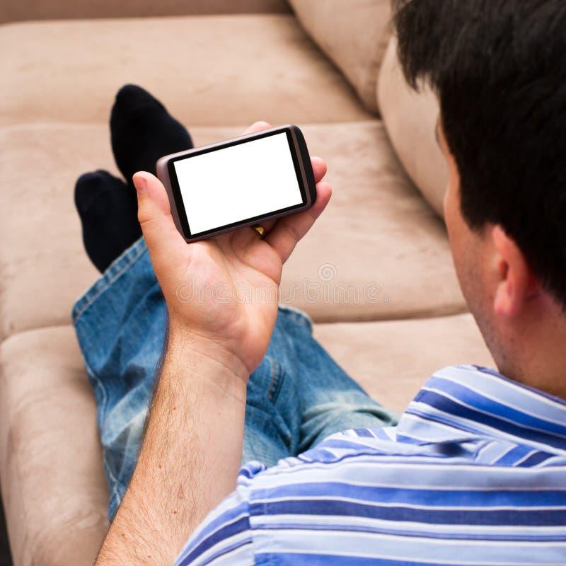 Un hombre que se relaja en un sofá que mira un smartphone fotografía de archivo