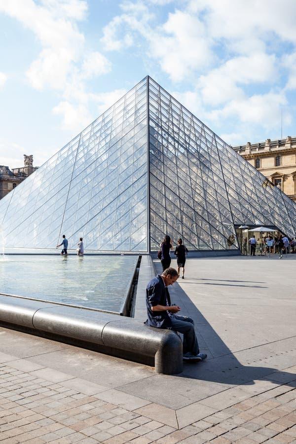 Un hombre que se sienta al lado de la pirámide de cristal del Louvre imagen de archivo