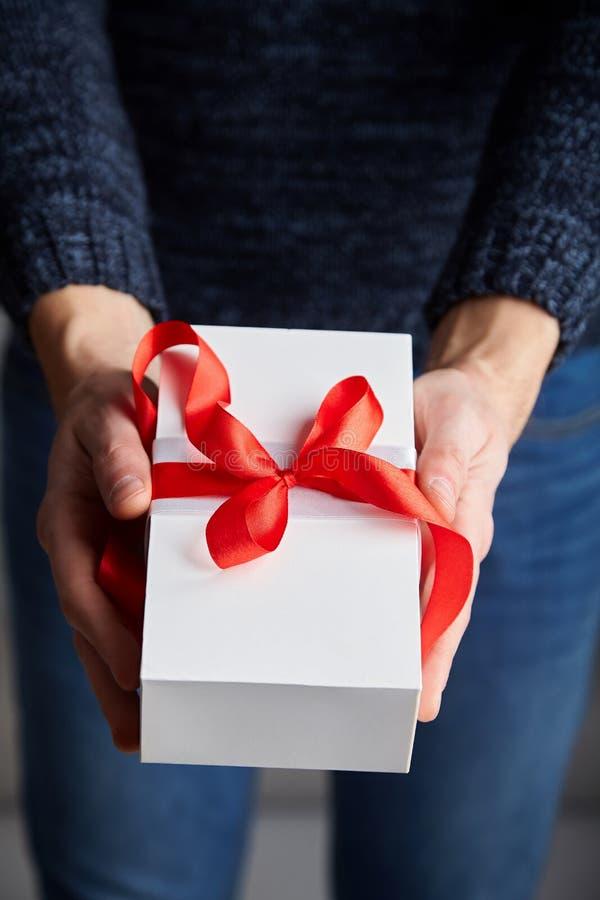 Un hombre que sostiene la caja de regalo blanca con la cinta roja en sus manos imagen de archivo