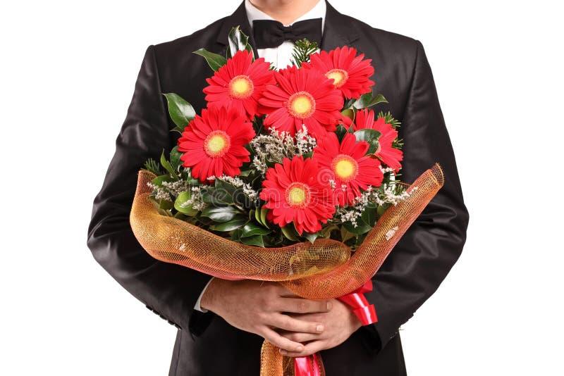 Un Hombre Que Sostiene Un Ramo Grande De Flores Imagen De