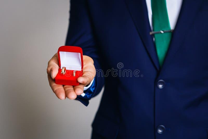 Un hombre que sostiene una caja con los anillos de bodas fotografía de archivo libre de regalías