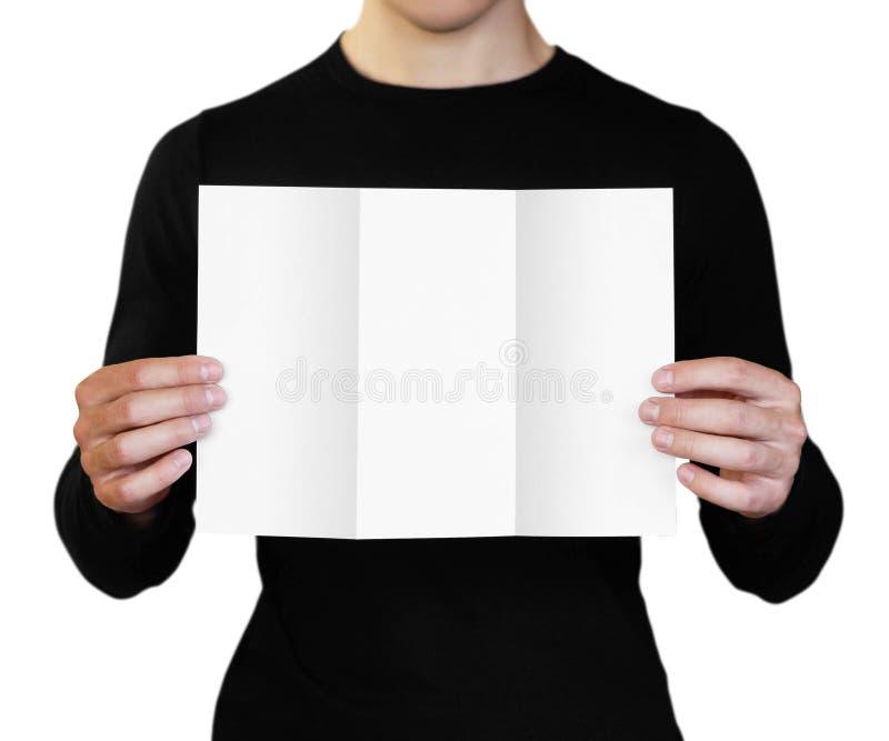 Un hombre que sostiene una hoja de papel blanca Sostener un folleto Cierre para arriba Aislado en el fondo blanco foto de archivo