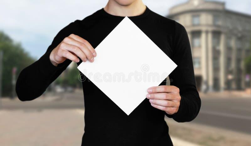 Un hombre que sostiene una hoja de papel blanca Sostener un folleto Cierre para arriba El fondo de la ciudad imagen de archivo