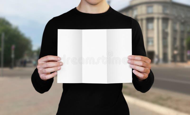 Un hombre que sostiene una hoja de papel blanca Sostener un folleto Cierre para arriba El fondo de la ciudad imagenes de archivo
