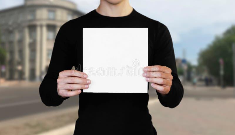 Un hombre que sostiene una hoja de papel blanca Sostener un folleto Cierre para arriba El fondo de la ciudad fotos de archivo