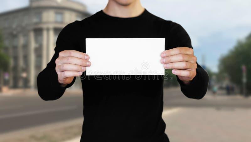 Un hombre que sostiene una hoja de papel blanca Sostener un folleto Cierre para arriba El fondo de la ciudad imagen de archivo libre de regalías