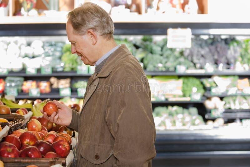Un hombre que sostiene una manzana imagen de archivo