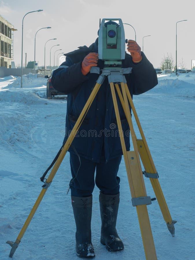 Un hombre que trabaja con un teodolito en la construcción de una casa imagen de archivo