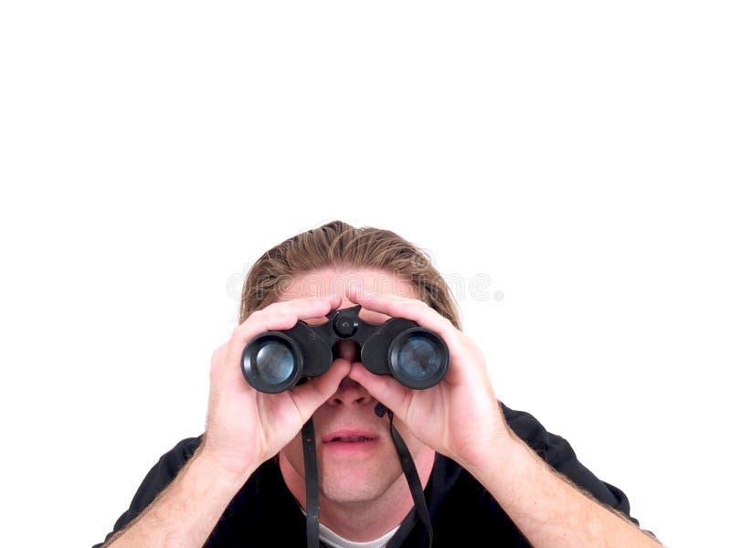 Un hombre que usa los prismáticos aislados imagen de archivo libre de regalías