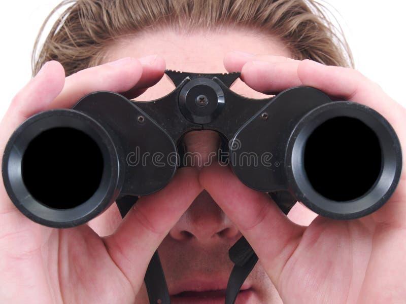 Un hombre que usa los prismáticos aislados foto de archivo libre de regalías