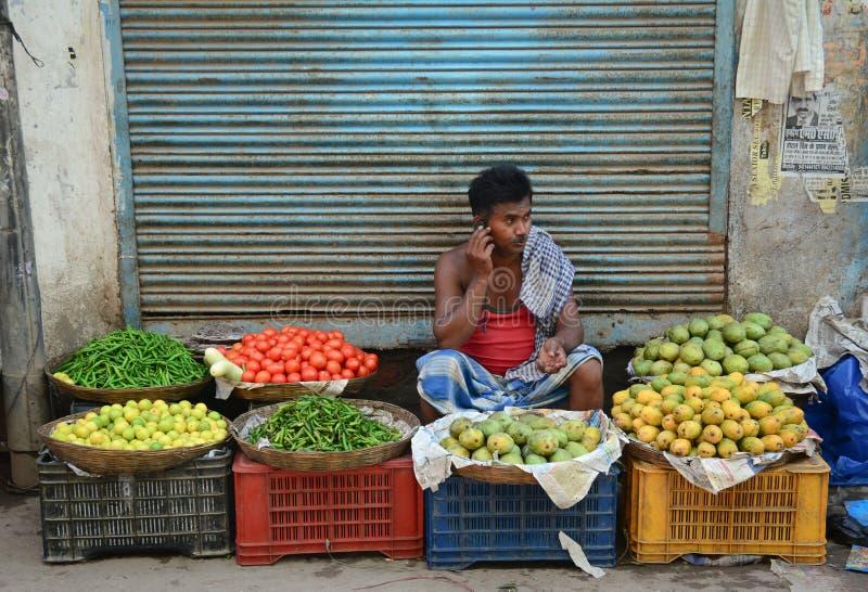 Un hombre que vende las frutas frescas en el mercado en Delhi, la India imagenes de archivo
