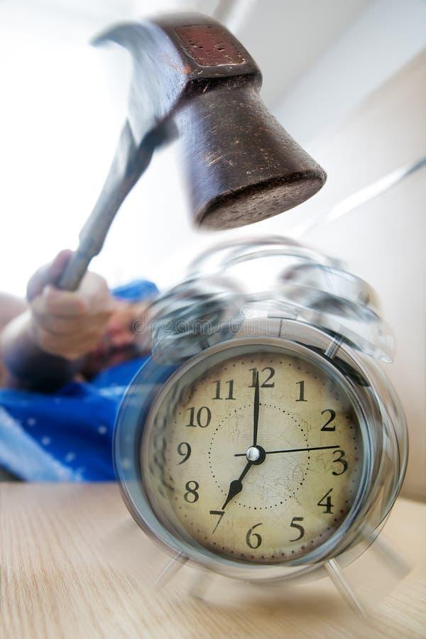 Un hombre quiere romper el despertador con el martillo imagen de archivo libre de regalías