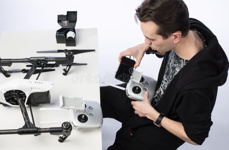 Un hombre recoge el quadcopter foto de archivo