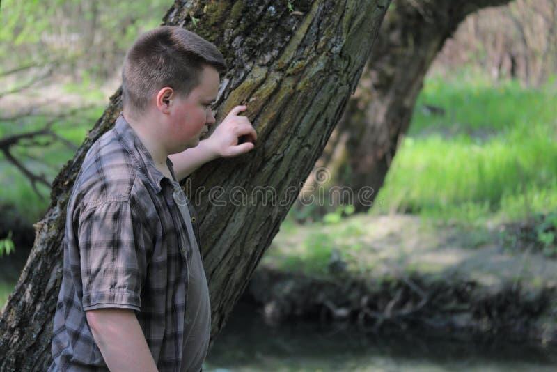 Un hombre regordete joven puso su mano en un tronco de árbol Colocación en los bancos del río que mira el agua En el parque entre foto de archivo