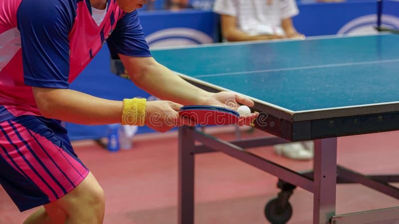 Un hombre rosado de la camisa está sirviendo una bola durante un juego del pingpon imagen de archivo libre de regalías