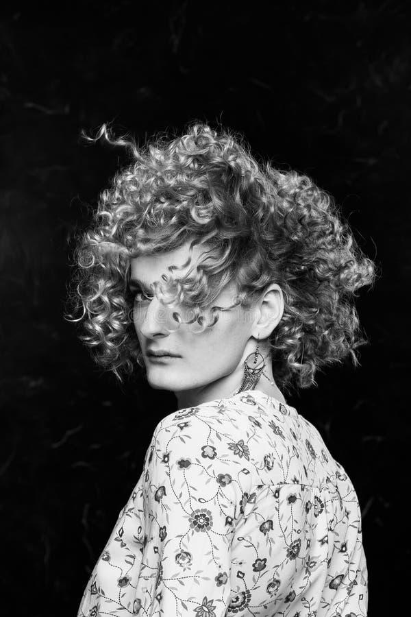 Un hombre rubio joven que el androgyn en la imagen de una mujer atractiva da vuelta con eficacia, el viento agita su pelo fotos de archivo