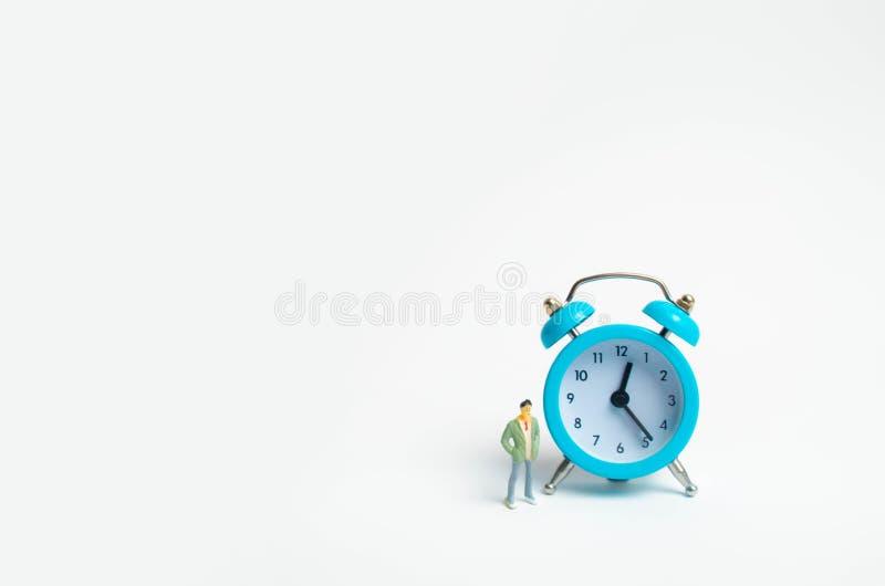 Un hombre se coloca cerca de un despertador azul y espera alguien El concepto de esperar una reunión, una fecha Atrasado y puntua foto de archivo
